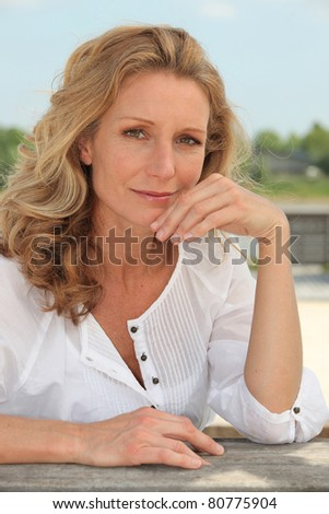 Reflective woman with long blonde hair sitting outside