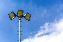 Reflector light for playground on blue sky background. Halogen light on metal pole. Stadium lights reflectors