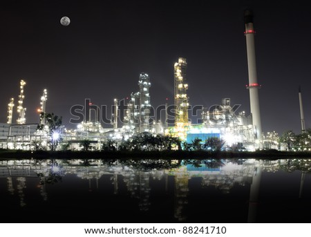 Reflex from oil refinery plant and full moon - stock photo