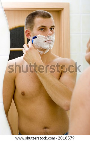reflexion of shaving young man in the bathroom's mirror