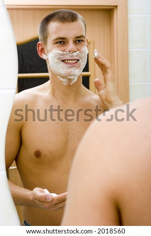 reflexion of young man in the bathroom's mirror with shave foam on face