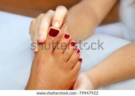 Reflexology woman feet massage therapy red fingernails