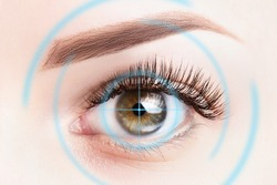 Refractive surgery, eye laser surgery concept. Female eye close up with blue laser rays.