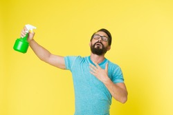 Refresh concept. Bearded man with eyeglasses refresh sprinkling water. Man refresh with spray bottle yellow background. Time to refresh yourself. Heat season. Hot and thirst. On guard of freshness.