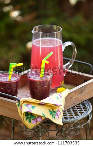 Refreshing berry drink in jar and glasses