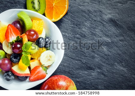 Refreshing bowl of fresh tropical fruit salad with ingredients on a textured slate kitchen counter with copyspace, overhead view