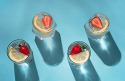 Refreshing cocktail with lemon, strawberries and ice cubes on bright blue table. Summer cold drink with sunlight shadows. Top view, flat lay