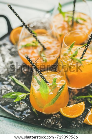 Refreshing cold alcoholic summer citrus cocktail with orange, peppermint and crushed ice in stemless glasses on dark tray over light wooden background, selective focus, vertical composition #719099566