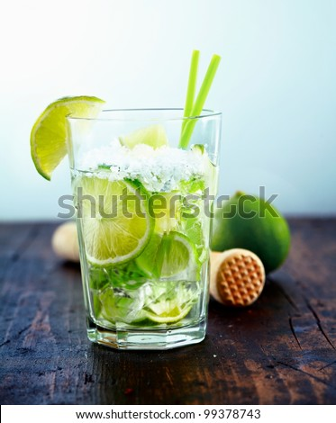 Refreshing cold Caipirinha with fresh lime slices and ice.