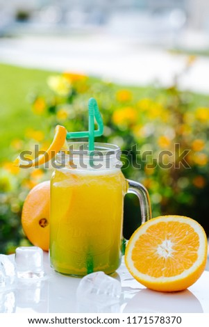 Refreshing cold cocktail with orange and crushed ice on white table #1171578370