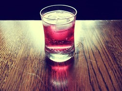 Refreshing cold red soda drink with lots of ice. Soda drink in a small glass. Soda drink is transparent and bubbles can be seen. A red reflection can be seen on the wood. There is a black background.