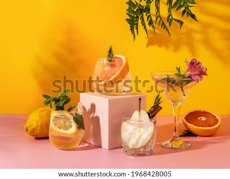 Refreshing colorful summer drinks with various fruits: pear, grapefruit, lemon on yellow background with shadow fern. Paloma cocktails. Hard seltzer cocktails Foto stock ©