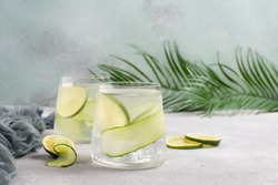 Refreshing detox water with fresh cucumber and slices of lime on grey concrete table with palm leaves.Healthy cucumber cocktail.