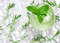 Refreshing drink with mint leaves in large wineglass surrounded by ice cubes. Close-up, top view. Cold mojito. Ice lemonade