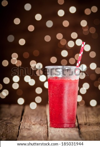 Refreshing ice cold glass of ripe red strawberry smoothie blended with low fat yoghurt for a healthy summer drink against a twinkling bokeh of party lights in the darkness