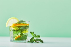 Refreshing ice mint cocktail with ice cubes, orange and lemon slices, drink for hot summer days. Fresh cool lemon-mint water, cocktail, detox drink, lemonade in glass jar and glass
