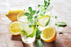 Refreshing iced mint tea with lemon and ice cubes, a drink for hot summer days selective focus, toned image