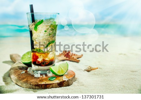 Refreshing iced rum, lime and mint mojito cocktail standing in a tall glass on an old wooden board on the golden sand of an idyllic tropical beach to celebrate a summer vacation
