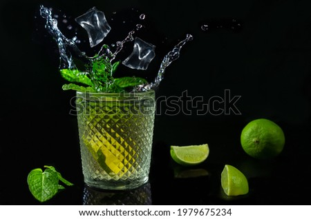 Refreshing mojito cocktail with ices cubes splash with fresh limes and mint on dark background.Studio shot of tropical drink with copy space. Foto stock ©