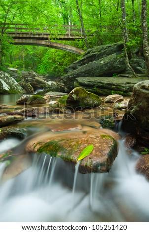 Refreshing Mountain Stream and Wooden Craftsman Pedestrian Bridge over Boone Fork Creek in the Blue Ridge Mountains of Western North Carolina