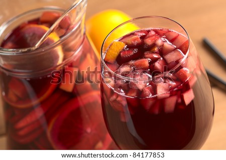 stock photo : Refreshing red wine punch called sangria mixed with orange, apple, mango pieces served in wine glass (Selective Focus, Focus on the fruit pieces in the middle of the glass)