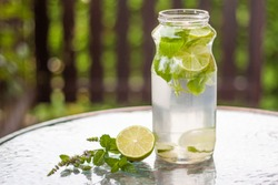 Refreshing sugar free beverage made out of ice cold water, lime juice, slices of lime and fresh organic herbs from the garden, mint and lemon balm. Perfect healthy drink on hot summer days.
