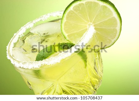 Refreshing summer cocktail drink with limes and ice isolated on green gradient background with copy space.