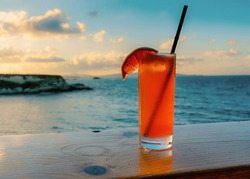 Refreshing summer cocktail - Paloma. Against a sunset over the sea.