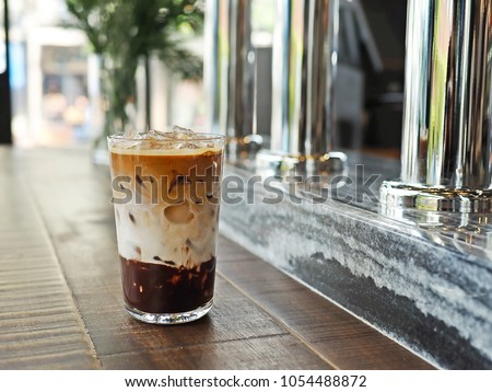 Refreshing summer drink concept a glass of three layers iced mocha latte at nice coffee shop with beautiful blurred background of coffee tap counter. (close up, selective focus, space for text)
