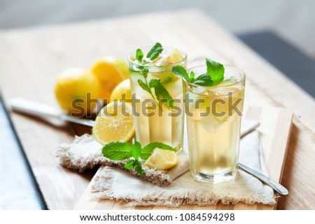 Refreshing summer drink with lemon, mint and ice. Glasses with cold and healthy beverage, place for text #1084594298
