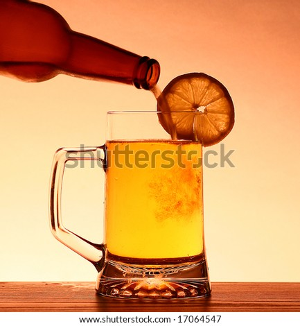 Refreshing Summer pint of beer being poured with lemon