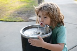 Refreshment solution. Thirsty kid drink water from drinking fountain. Thirst quenching