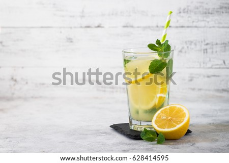Refreshment Summer drink. Traditional  lemonade with lemon mint and ice on white.