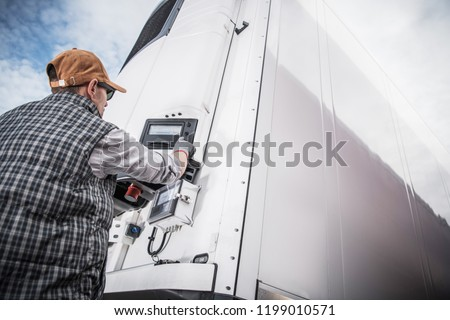 Refrigerated Semitrailer Cargo. Adjusting Temperature by Caucasian Truck Driver.