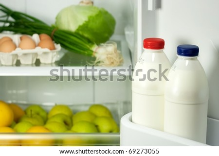 Refrigerator full with some kinds of food - fruits, vegetable, eggs and milk