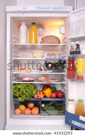 refrigerator full with some kinds of food - vegetables, meat, fish - stock photo