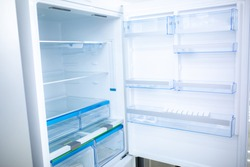 Refrigerator. Open door of an empty fridge. Household appliances in the store. Electrical equipment and household goods. Kitchen appliances in the mall.