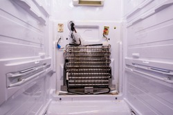 Refrigerator repair. Freezer compartment back panel removed. Evaporator coils with a frozen thermostat