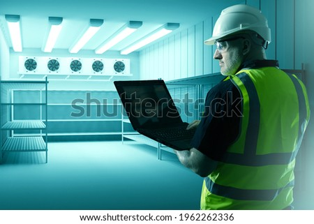 Refrigerators compartment. Warehouse with shelves for food storage. Grocery warehouse with air conditioning. Stelms with shelves.  Industrial refrigerator. Engineer sets up refrigeration equipment. Foto stock ©
