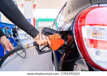 Refuel cars at the fuel pump. The driver hands, refuel and pump the car's gasoline with fuel at the petrol station. Car refueling at a gas station Gas station Foto stock ©