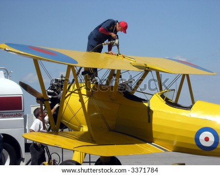 Refuel the plain. Show people and their work. Technician refueled the vintage airplane in between the flights.
