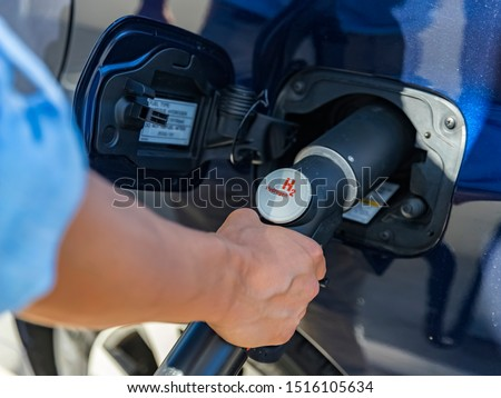 Refueling the car with hydrogen at a hydrogen fuel station