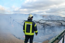 Refugee camp burns in Bosnia and Herzegovina. Migrant camp Lipa near Bihac has been destroyed in a fire. The camp had housed more than 1,300 people. Sign: Feuerwehr -  Fire Department.