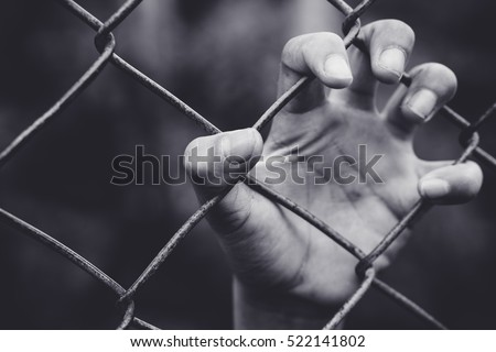 Refugee children hand on fence. Refugee concept.Dark tone.Black and white vintage tone. #522141802