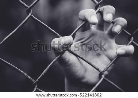 refugee children hand on fence. ...