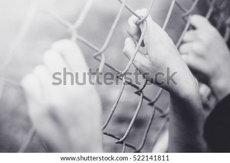 Refugee children hand on fence. Refugee concept.Dark tone.Black and white vintage tone. #522141811