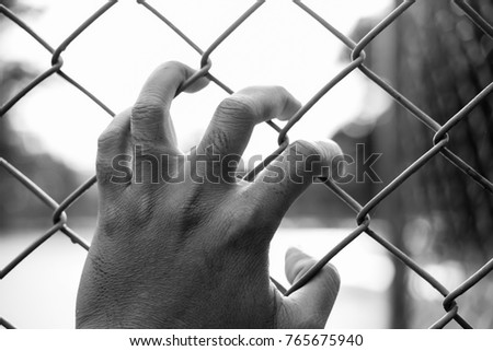 Refugee man hand on fence. Refugee concept.Dark tone.Black and white vintage tone. #765675940