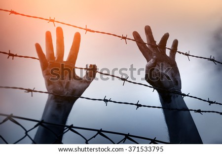 Shutterstock Refugee men and fence. Refugee concept