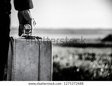 Refugee woman going with her old suitcase on the road in the Nordic landscapes Stock photo ©