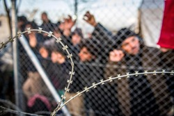 Refugees waiting behind barbed wire fence